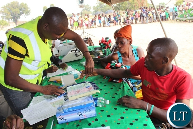 National Registration Senanga District Registrar David Singalamba (l) taking finger prints of an applicant during the launch of Phase II of the 2015-2016 Mobile National Registration Card Exercise in Nalolo District, Western Province