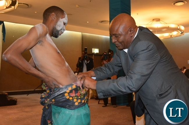 Zambia Bureau of Standards Laboratory Manager Nicodemus Malisa shows appreciation to a dancer from twatasha cultural group during the Zambia Bureau of Standards launch of the new logo at hotel intercontinental