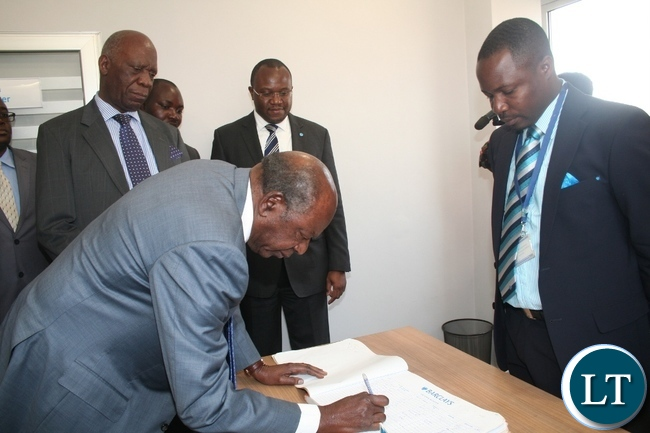 Finance minister Alexander Chikwanda singing in the visitors book during the official opening of Barclays Solwezi Branch as Barclays Bank Zambia Board chairman Jacob Sikazwe (I) and Barclays Zambia managing director Saviour Chibiya (m) and Solwezi Barclays Bank Branch manager Chomba Musonda (r ) look on in Solwezi