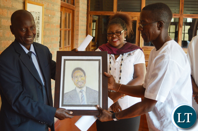 Mazabuka based artist Alec Lishandu (right) handles over an artistic portrait of President Edgar Lungu to Choma district administrative officer Vincent Sikanyela while Choma Museum director Bevine Sangulube looks on during opening of an art exhibition at the museum