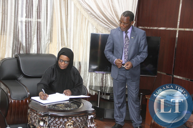 First Lady Esther Lungu signs a visitors book when she paid a courtesy call on Zambia's Ambassador to Saudi Arabia Ibrahim Mumba as Zambia deputy Ambassador to Saudi Arabia Tom Mwila (R) looks on at Zambia's Embassy in Riyadh, Kingdom of Saudi Arabia on Monday, October 12,2015 -Picture by THOMAS NSAMA/STATE HOUSE