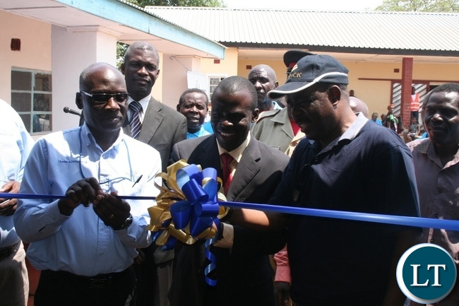 Solwezi acting district commissioner Chipawa Chipawa (m) with chief Mumena (right in a cap) and Lumwana mining company community relations superintendent Harrington Kanema (l) cutting a ribbon during the official handover of Mukamena Multipurpose cooperative centre which has been constructed by Lumwana mining company at Mutanda at a total cost of K240,000