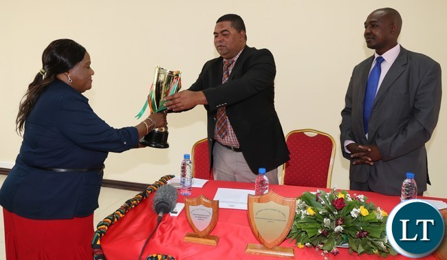 National Sports Council of Zambia Board Member Matilda Mwaba presents some independence tournament Trophies to Lusaka Province Minister Obvious Mwaliteta while his Deputy PS Japhen Mwakalombe looks on in Lusaka