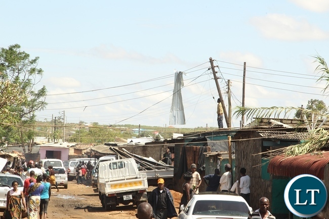 Baulini Residents looking at the roof on the ZESCO after it was blown off due to heavy rains in Baulini