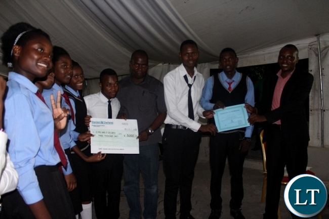 2nd Position in the Competition and Consumer Protection Commission School Clubs debate St. Johns Secondary School pose for a photograph with Western Provincial Competition and Consumer Protection Commission Investigator Mutemwa Nakambowa (r) and Mongu District Education Board Secretary Mulonda Sendoi (c)