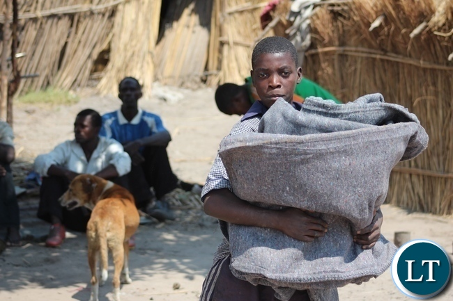 A boy of Imuba Village collects blankets as relief support from DMMU to victims of a firestorm which burnt the entire village to ashes in Lower Katongo area in Mongu.