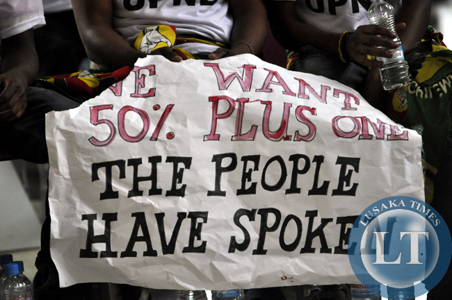 A woman from the UPND displays a placard, demanding for the inclusion of the 50 plus one percent clause in the draft Zambian constitution