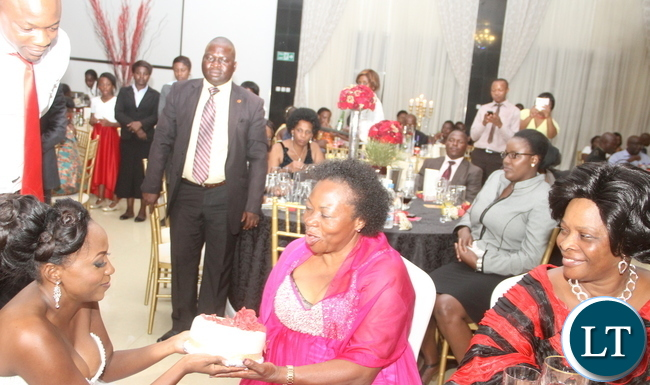 Chifubu PF Member of Parliament Susan Kawandami's receives a cake from her daughter Chinyimba as Former Zambia Army Commander General Benjamin mibenge's son Bweupe (L) and First Lady Esther Lungu looks on during a wedding for Bweupe and Chinyimba at ZAF Chamba Valley Officers' Mess in Lusaka on Saturday, November 14,2015