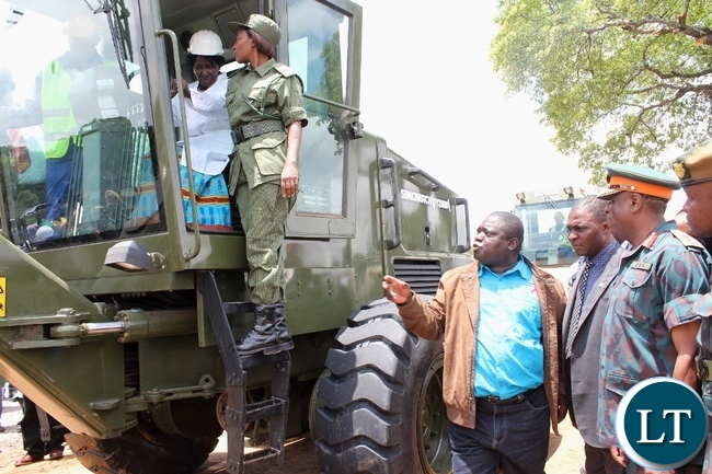 Acting President Inonge Wina operating a grader for Zambia National Service (ZNS) as Works and Supply Minister Yamfwa Mukanga (c) and ZNS Commandant Lt. Gen. Nathan Mulenga (r) observe during the launch of Countrywide Feeder Roads Rehabilitation Project worth K16.2 billion in Litoya area of Nalolo District in Western Province t