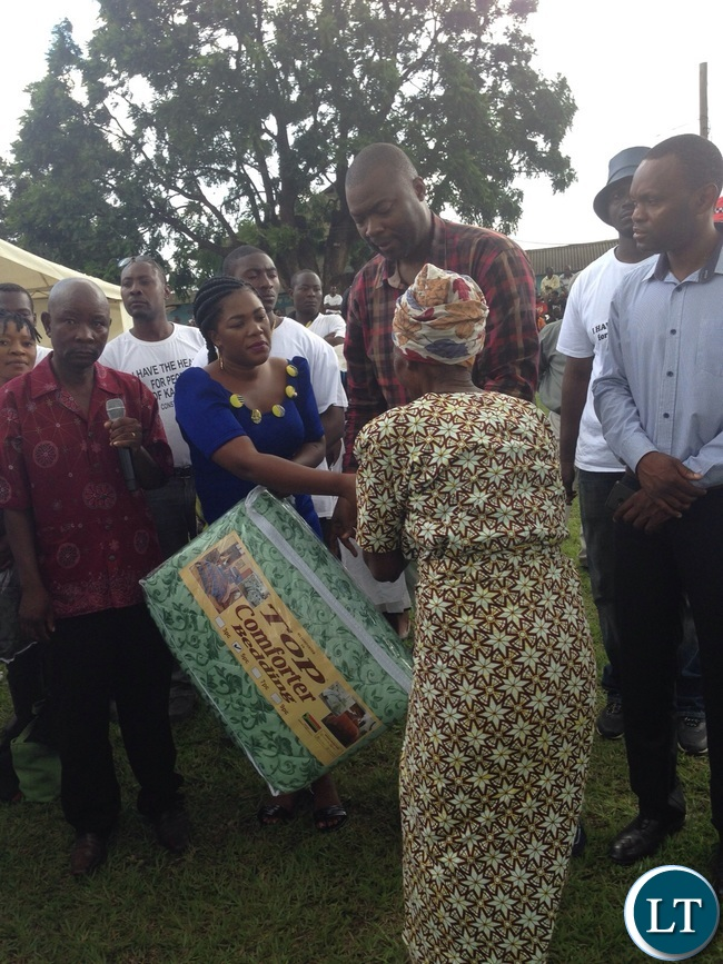 Mr Lusambo flanked by the wife handing over the items