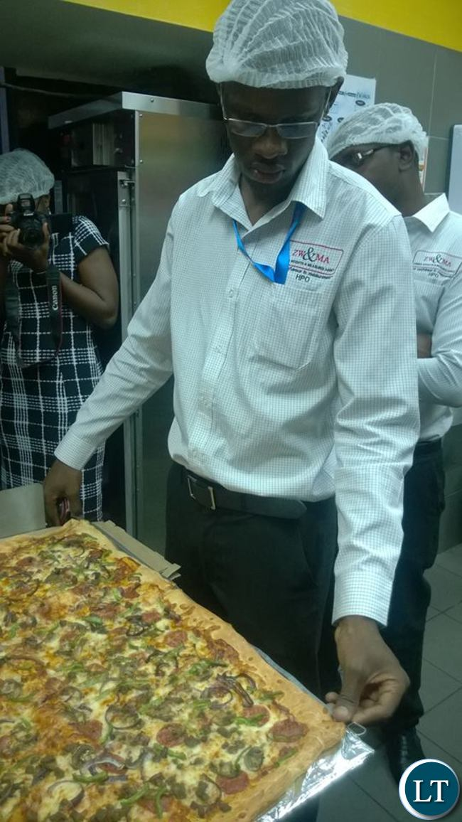Zambia Weights and Measures Agency officers measuring the pizza