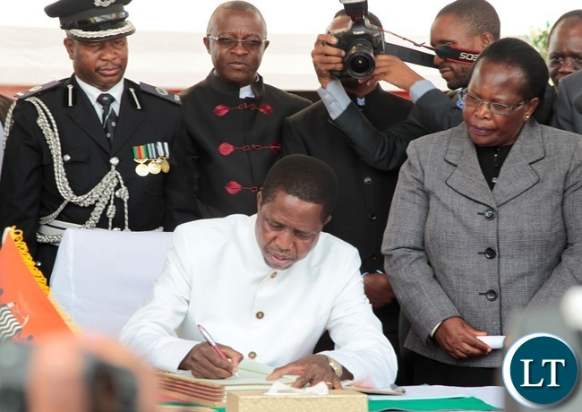 President of the Republic of Zambia, Mr. Edgar Chagwa Lungu signing the Constitution Bill whilst Chief Justice Irene Mambilima looks on during the Assenting of the Constitutional Bill Ceremony at Heroes Stadium yesterday 05-01-2016. Picture by ROYD SIBAJENE/ZANIS