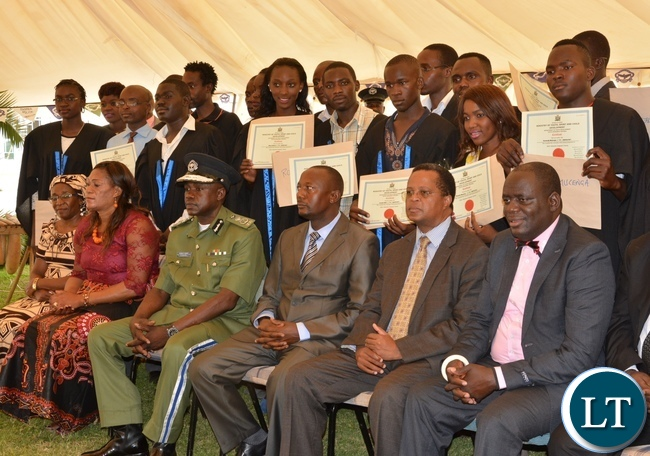 Graduates at Lusaka youth resource center pause for photo with the Acting Permanent Secretary Ministry of Youth Sport and child Development Mr. Alfonso Banda and the Deputy inspector general of police Mr. Engine Sibote
