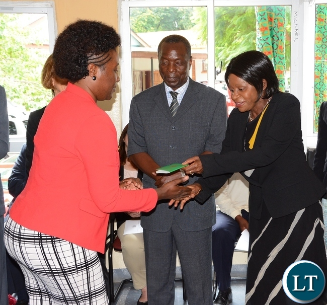 Ministry of Home Affairs Permanent Secretary Elwyn Chomba gives Marie Reine Rutagwera resident permit whilst her Deputy Permanent Secretary Willies Manjimela (c) looks on during the launch of Integration for Former Rwandan Refugees at the Commissioner for Refugees Conference room