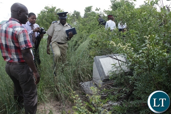 Western Province Zambia Police inspecting demolished tomb stones on grave sites by encroachers who are building houses in the old Mongu Cemetery yesterday. Government has warned against all illegal activities happening in the old cemetery.