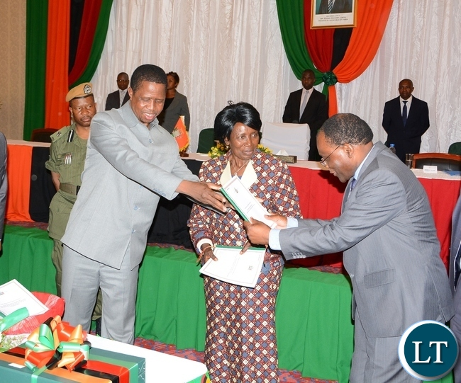President Eedgar Lungu gives the document to Secretary to the Cabinet Rowland Msiska Whilst Vice President Inonge Wina (C) Looks on during the Launch of the Perfromance-Based Contract system for Permanent secretaries at Government Complex