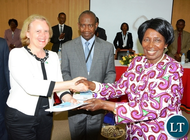 Vice President Inonge Wina gives UN Resident Coordinator Janet Rogan whilst DMMU Coordinator Patrick Kangwa (c) looks on during the Launch of the Disaster Management Policy and Settlement at Government Complex