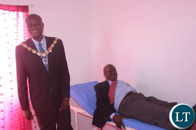 Kabwe District Commissioner Patrick Chishala (on the bed) trying out the bed at the newly commissioned Kamakuti Health Post in Kabwe.(left) Kabwe Mayor Richard Bango waits for his turn.