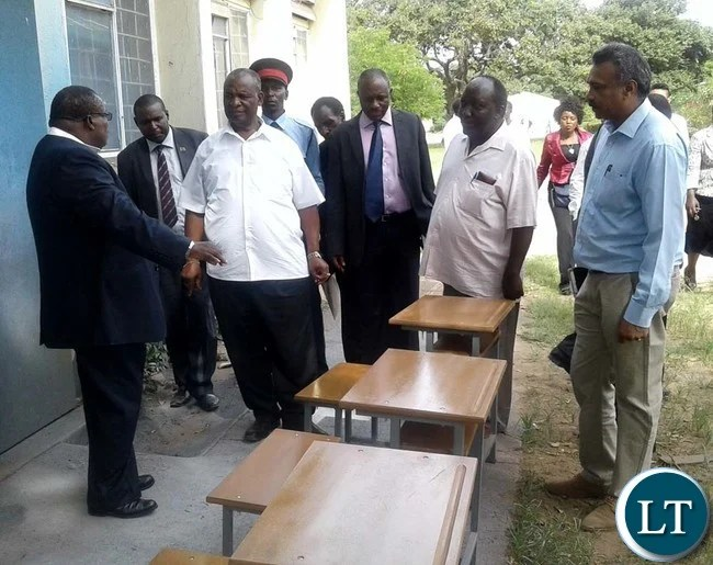 CHOMA Trades Training Institute principal Tom Kapamba (left) shows Southern Province deputy Permanent Secretary Douglas Ngimbu (middle), Higher Education Minister Michael Kaingu (in white shirt) and College vice board chairperson Subi Thomas (far right) some school desks being made by carpentry students at the College