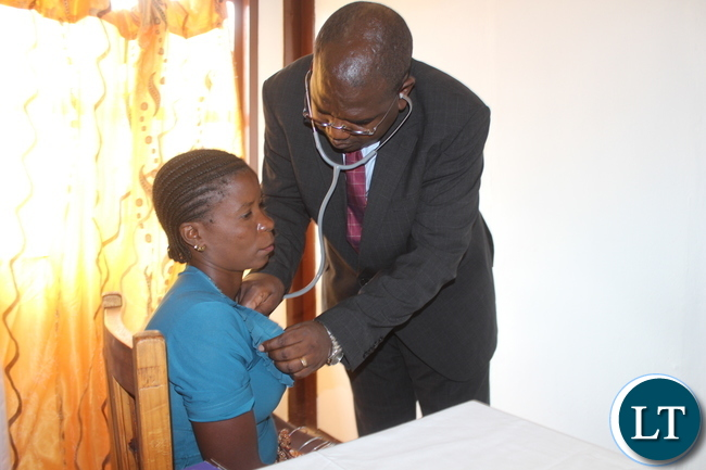Deputy Minister of Health Dr Chitalu Chilufya attends to the first patient Ms Eustance Chiyumba at the newly opened Muunyumabisi Health Post in Monze District yesterday. The Health Post was constructed by Megha Engineering and Infrastructure Limited of India.