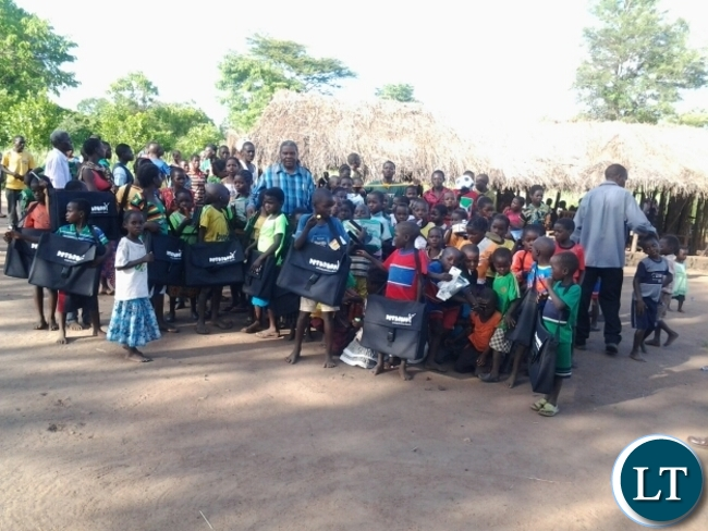 Malambo Patriotic Front Member of Parliament Jacob Shuma with Chitilila community school pupils in Mambwe.The grass thatched community school is serving a number of pupils who had not enrolled due to distances to the nearest schools.