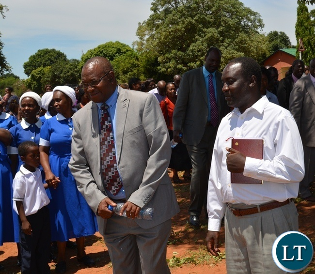 SDA South Zambia Conference president Maxwell Muvwimi (left) and Livingstone district planning officer Elvis Siyauya (right) about to cut a ribbon during the official opening of Victoria Falls Adventist Primary School in Livingstone