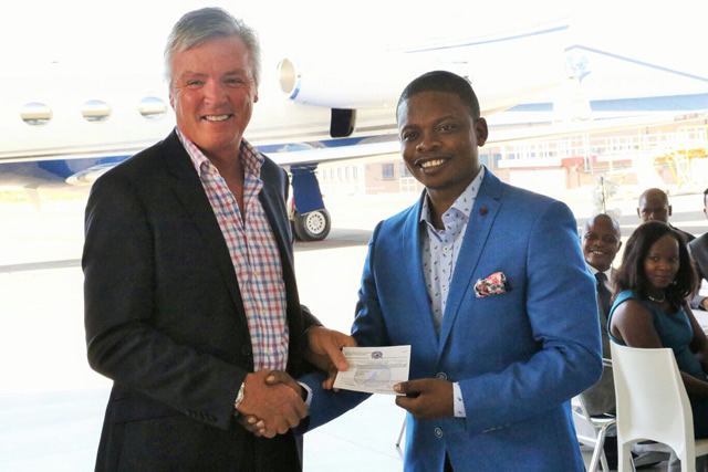 Gulf Stream Manager Larry Flynn presents the certificate of ownership to Prophet Bushiri