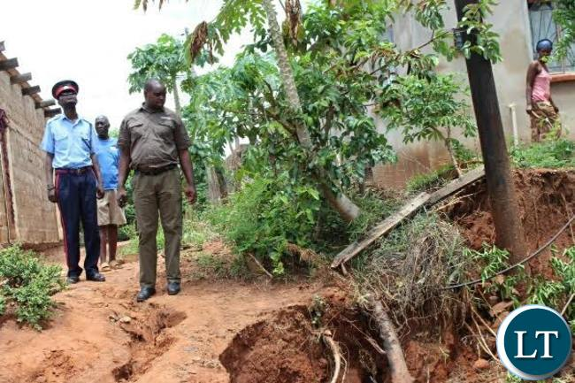 Livingstone District Commissioner Omar Munsanje inspects a loose Zesco pole that has been disturbed following heavy rains experienced in Livingstone