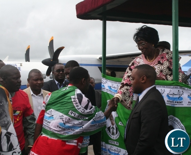 Vice President Inonge Wina (r )receives former Rainbow party North-Western province vice secretary Jones Kikuma (c ) as Patriotic Front deputy spokesperson Fr Frank Bwalya ( second left) looks on at Solwezi airport on Friday. Picture by BETRAM KAOMA /ZANIS