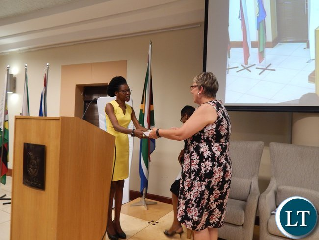 Zambia's Christabel Mwango presents a gift to USAID Southern Africa Mission Director Ms. Cheryl Anderson at the graduation ceremony of 130 youths from the Southern African region at the University of South Africa in Pretoria on 25th February, 2016