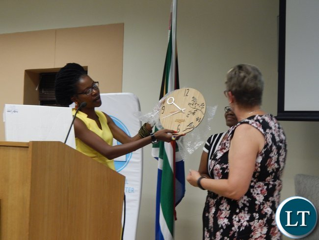 Zambia's Christabel Mwango shows a gift organised by the graduates to USAID Southern Africa Mission Director Ms. Cheryl Anderson at the graduation ceremony of 130 youths from the Southern African region at the University of South Africa in Pretoria on 25th February, 2016