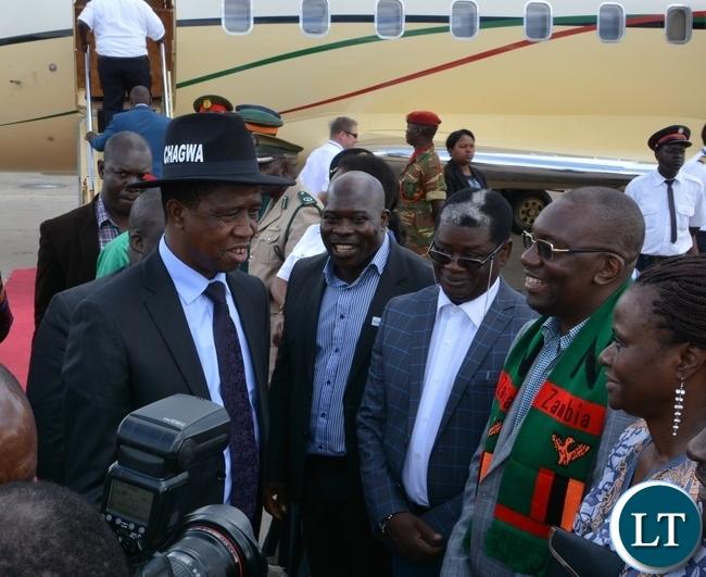 President Edgar Lungu speaks to Newly elected FAZ president Arron Kamanga on his arrival at Simon Mwansa Kapwepwe airport