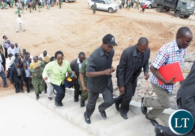 President Edgar Lungu (l) runs to climb the stairs to the bridge during the official commissioning of the Sioma Bridge built at a cost of K108.2million in Sioma District of Western Province