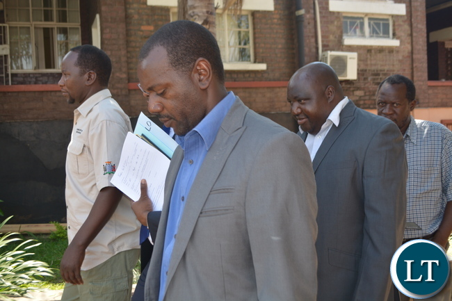 Milford Maambo hides behind his lawyer just after the Court hearing in Livingstone