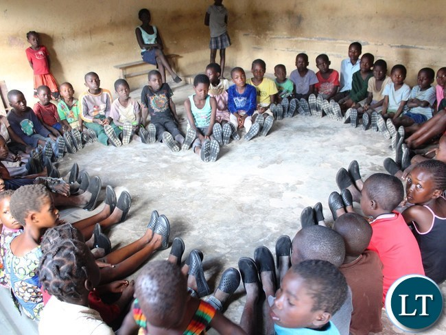 Part of the pupils who benefited from the  over 200 shoes expresses their happiness by making the love shape  for   Ubulayo Charity Organization Founder Tasila Lungu at Chiba Community School in Kasama district .This was after she made a donation of shoes to over 200 for vulnerable and orphaned pupils at the school.