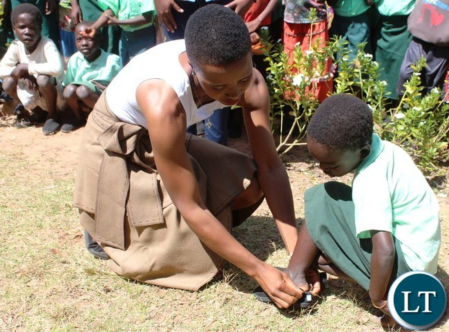 Ubulayo Charity organization founder Tasila Lungu with Mervis Chanda 8, a pupil at Mipango Community School in Mungwi district during her tour of Northern Province. This was after she made a donation of shoes to over 200 vulnerable and orphaned pupils at the school.