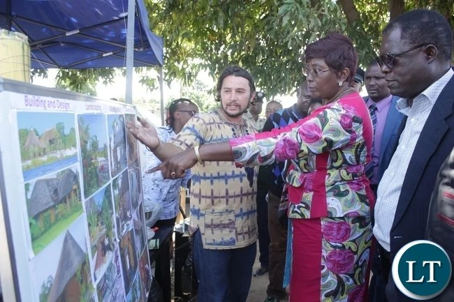 Malilkelelo Estates Limited Manager Gabriel Scholz (l) shows Community Development Minister Emerine Kabanshi (c) the pictorial display of building, design and landscaping services they offer during the 2016 Labour Day Celebrations at Mongu stadium