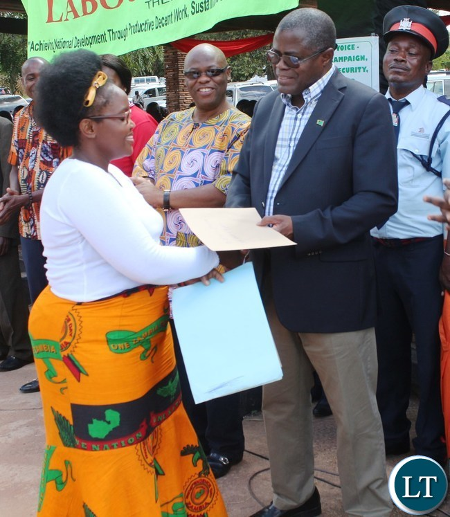 .Mines and Mineral resources Minister Christopher Yaluma presents an ward to a ZANIS officer Winnie Sakala for her hard work at President's Park in Kasama today during labour day celebrations. looking on is norther PS Hlobotha Nkunika