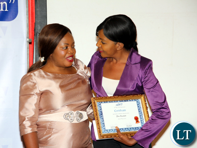 MISA Zambia chairrperson Hellen Mwale (l) confers with ZNBC's Ellen Hambuba during the 2016 MISA Zambia annual awards in Lusaka on April 29, 2016.