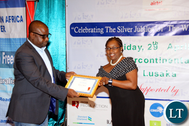 Times of Zambia journalist Stanslous Ngosa receives an award from Airtel Zambia representative Yuyo kambikambi during the 2016 MISA Zambia annual awards in Lusaka on April 29, 2016.