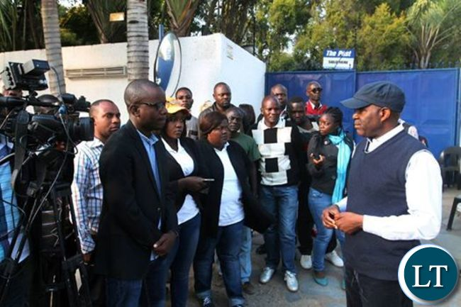 Fred Mmembe (in a cap) speaks to Journalists shortly after addressing workers on Thursday following the closure of the Post