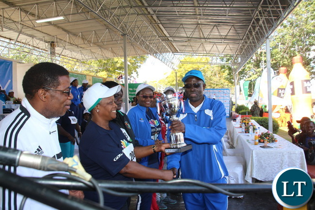 Zambia 1st lady Esther Lungu congratulating the Zambia Sugar Team leader Leonard Habasune as he receiving the overall winner trophy as ZAAA President Elias Mpondela is looking on during the Prize giving ceremony