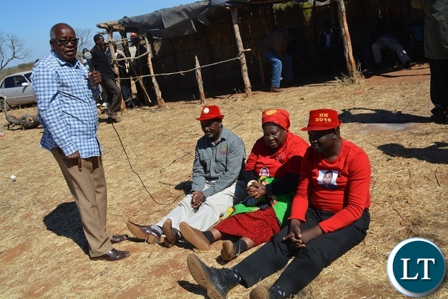 Former Southern Province Minister Daniel Munkombwe(holding microphone) counsels UPND Livingstone parliamentary candidate Mathews Jere(left in red hat) and mayoral candidate Eugene Mapuwo( seated third from left) during a rally to drum up support for UPND Presidential,parliamentary and local Government candidate at Mahululu clinic in Livingstone