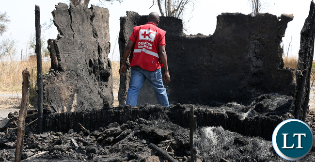 A Zambia Red Cross official checks the burned down house in Chikwato village in Namwala District, Southern Province, where 143 people have now been displaced in a wave of political violence. Nine village have been affected by the violence.