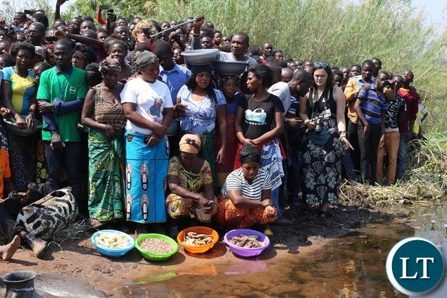 WOMEN lining up with traditional food to be offered to the ancestral spirits at Ng'ona river by the Mwata.