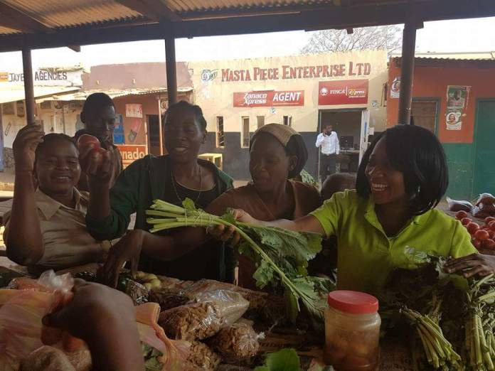 Mwansa Bwale at a market representing Zoona and telling women enterpreneurs about Zoonas campaign