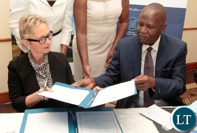 Minister of Finance Felix Mutate and World Bank Country Manager Ina-Marlene Ruthenberg exchange the documents after signing ceremony of the first amendment to the grant agreement of the Public Financial Management Reform and launch of the Zambia PEFA assessment 2016