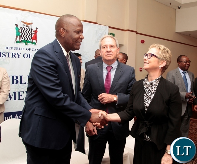 Minister of Finance Felix Mutate chats with World Bank Country Manager Ina-Marlene Ruthenberg after signing ceremony of the first amendment to the grant agreement of the Public Financial Management Reform and launch of the Zambia PEFA assessment 2016 whilst Stephan Neu-KfW looks on