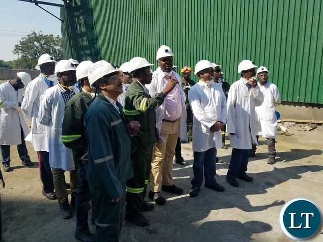 Copperbelt Minister Bowman Lusambo listens to a KCM Engineer during the tour of the Smelter Plant