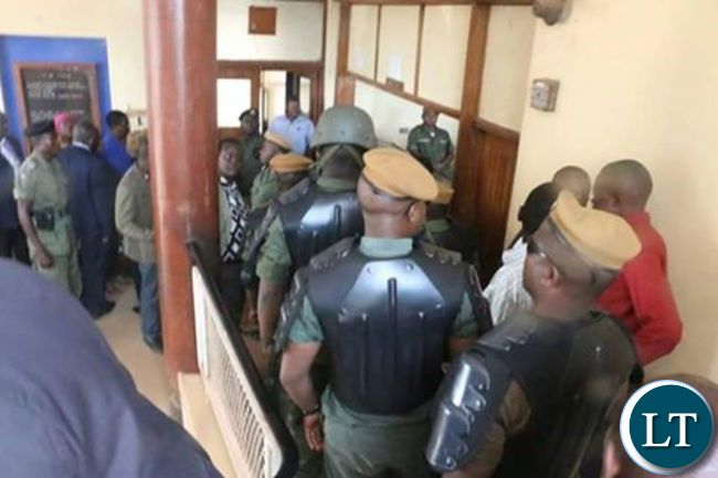 Police officers leading HH and GBM (not in picture) in police cells